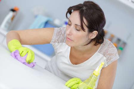 desinfectante: superficie de la limpieza del ama de casa de la mesa con un desinfectante