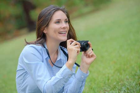 mujer alegre: Mujer en el parque que toma la fotografía Foto de archivo