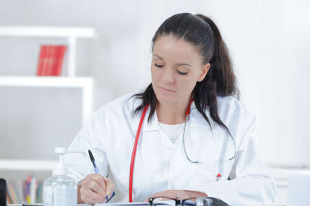a lady doctor: portrait of young female doctor sitting at desk in hospital Stock Photo
