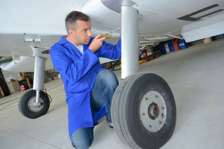 underbelly: Man working on underside of aircraft