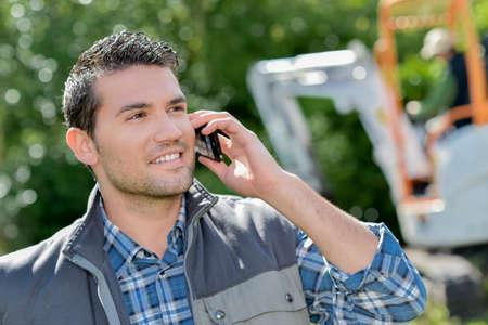 paysagiste: Man en plein air sur le téléphone, pelle en arrière-plan