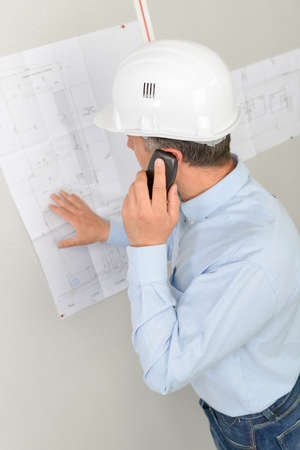 Man on telephone, looking at plans pinned on wall