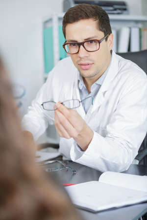 ocular: attractive young optometrist during consultation with patient