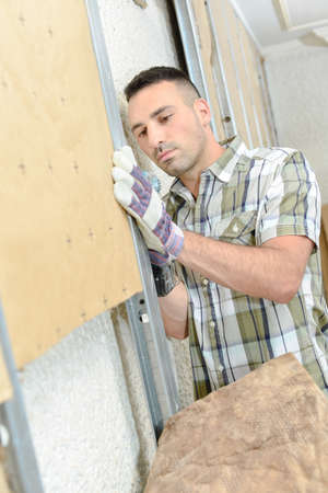 rockwool: Man fitting insulation into wall