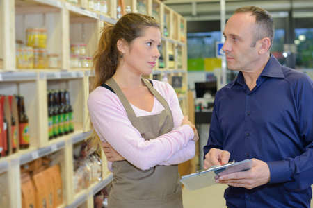 Man holding clipboard, sales assistant looking reproachful Stock Photo