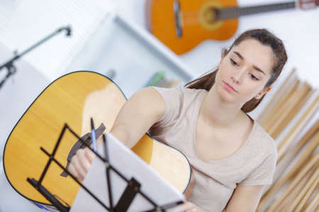 woman on couch: beautiful young woman on the couch with a guitar