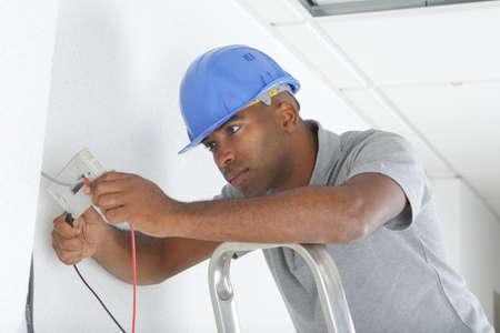 electricidad industrial: hombre de cableado de la instalación Foto de archivo