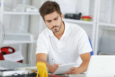 hobs: young engineer taking notes while developping new induction hobs Stock Photo