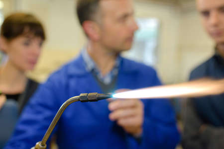 fmale: ironworks teacher showing students how to securely use gas welder