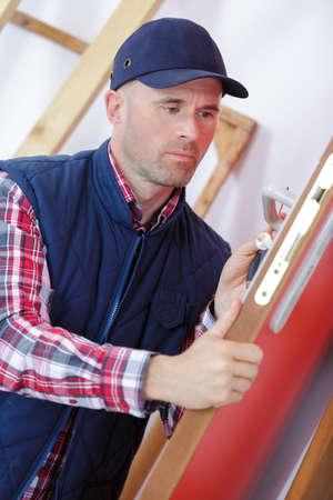 deadbolt: male carpenter worker at interior wood door lock installation