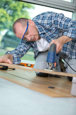 carpenter cutting laminated planks for layered parquet using bandsaw Stock Photo