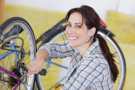 screw key: woman hand repair bicycle whee with screw key Stock Photo