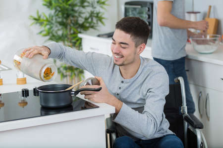 move in: disabled young man in wheelchair in the kitchen Stock Photo