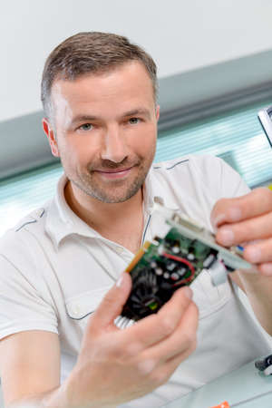 itc: PC repair man holding a graphics card