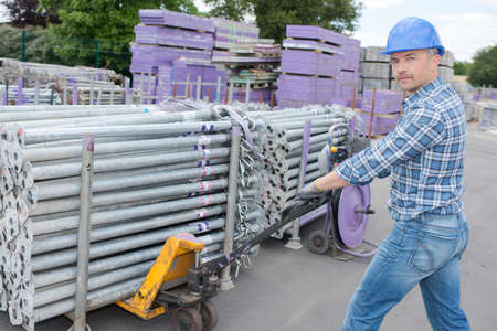 andamios: Man pulling pallet truck Foto de archivo