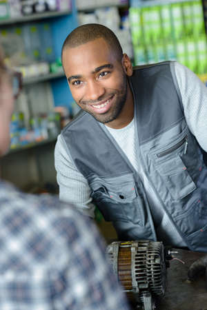 Male retailer smiling at customer Stock Photo