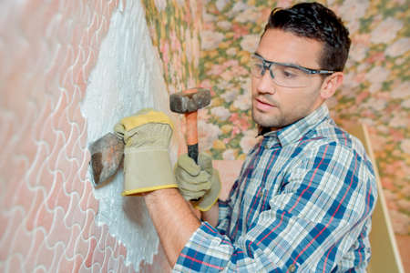 Man chipping tiles off a wall Stock Photo
