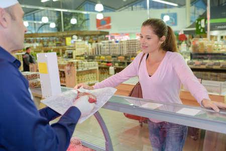 siervo: Señora de comprar carne de carnicería Foto de archivo