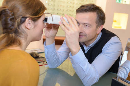 eyepiece: side view of an optician doing sight testing for client