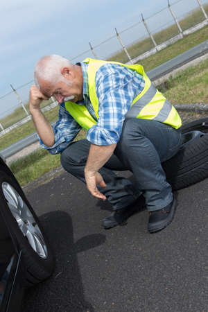 discouraged retired man unable to change car tyre Stock Photo