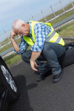 crestfallen: discouraged retired man unable to change car tyre Stock Photo