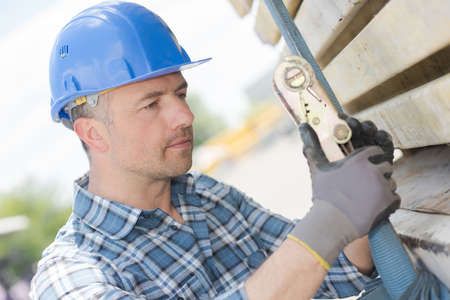 attaching: Man attaching load with ratchet strap Stock Photo