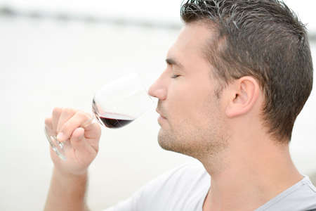 degustating: Man smelling a glass of red wine