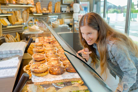 woman pointing at a pastry