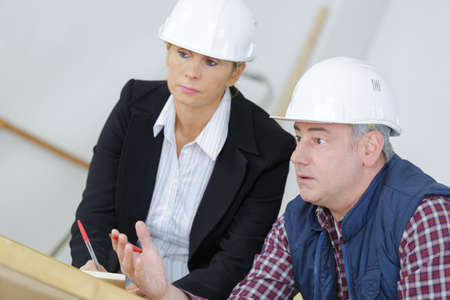 foreman: a female architect and a foreman examining blueprints Stock Photo