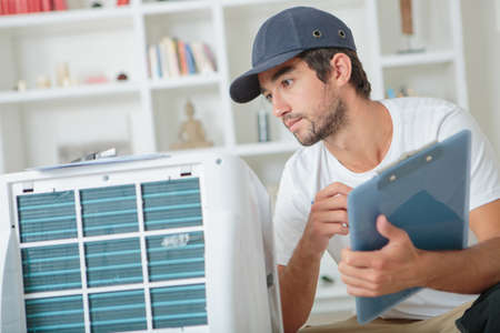 electricity company: handsome technician checking the ac at clients home Stock Photo