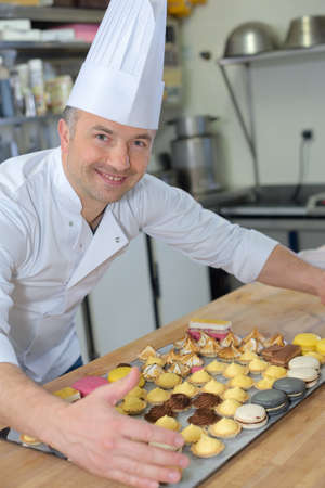 pastry chef holding delicious looking cakes and pastries