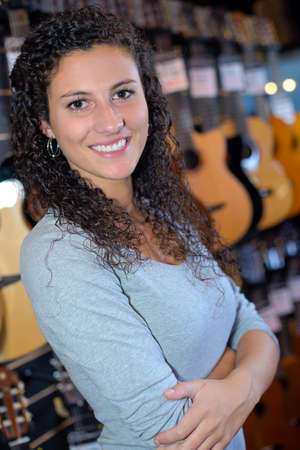accoustic: Portrait of woman in musical instrument shop