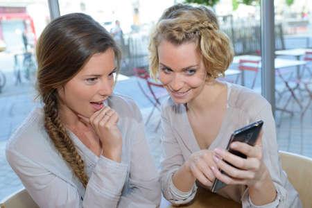 amabilidad: friends looking at smartphone in cafe Foto de archivo