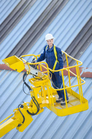 picker: Woman in cherry picker cage Stock Photo
