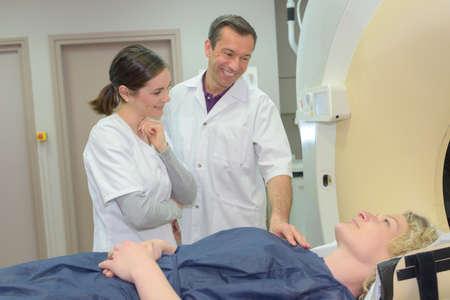 reassuring: Medical workers reassuring patient entering mri scanner