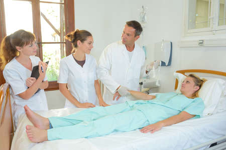 hospital patient: Medical staff around patient in hospital bed Stock Photo