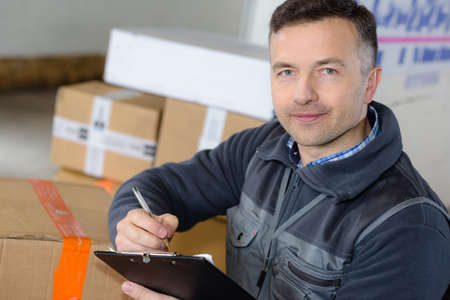 parcel: delivery man with parcel near cargo truck shipping service