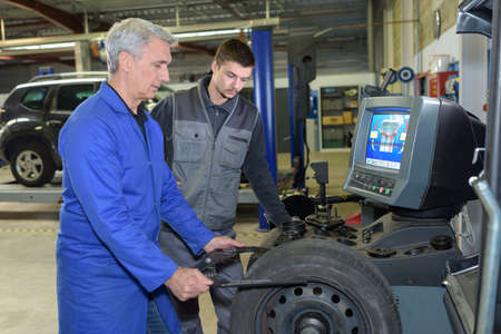recycles: apprentice mechanic and teacher retreading wheel in automotive workshop
