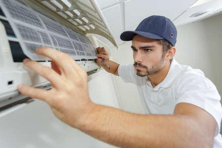 portret van medio volwassen mannelijke technicus die airconditioner herstelt Stockfoto