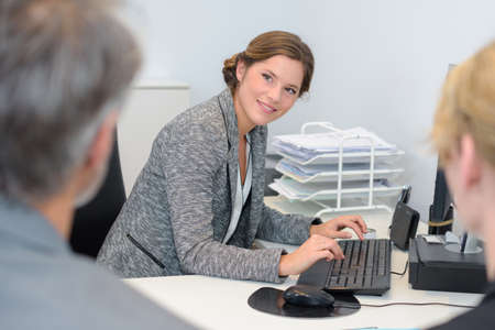 Lady typing while  in meeting with couple Stock Photo