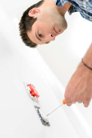 wall socket: Electrician with a wall socket