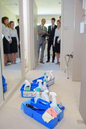 hotel staff: Hotel staff looking into room with cleaning products