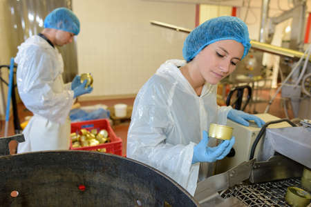 safety check: factory workers checking tinned food in factory