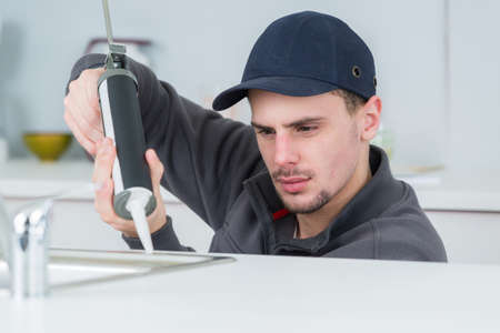focused young technician sealing sink in clients kitchen