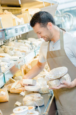 shop assistant: Shop assistant stocking cheese shelf