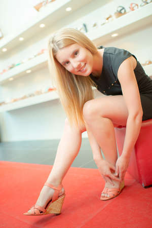 wedge: Lady trying on wedge heeled shoes in shop Stock Photo