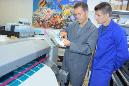 communication capability: Two men next to industrial printer