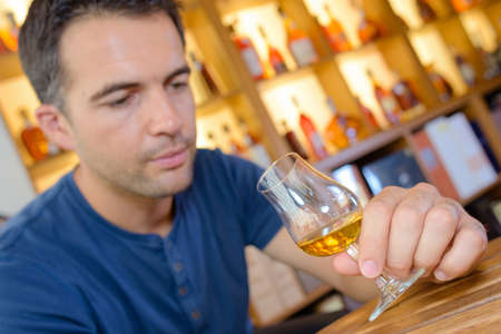 taster: Man looking into glass of alcohol