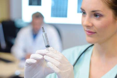 medical doctor: Closeup of nurse preparing syringe Stock Photo