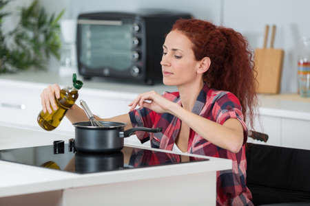 disabled woman cooking in her kitchen Stock Photo